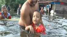 Menghilangkan Rasa Jenuh, Warga Berenang di Tengah Banjir